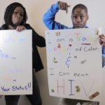 """Black women holding handmade signs reading """"I am a Trans women of color and I can beat HIV,"""" and """"Be Who You Are...Love Who You Are...Know Your Status!!"""""""