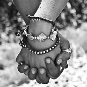 couple holding hands with fingers interlaced