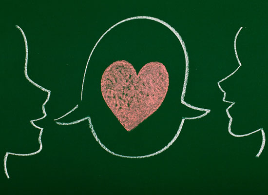 A chalk drawing of two people facing each other sharing a speech bubble with a heart in the center