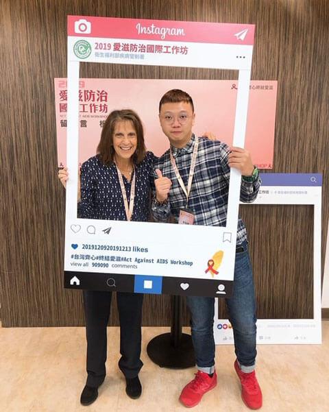 Two people pose behind a cardboard instagram frame