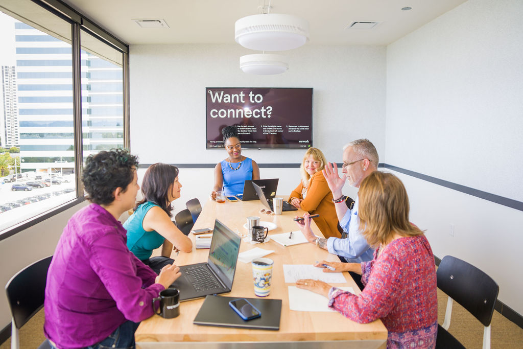 Six CAPTC staff members sitting around a conference table in discussion